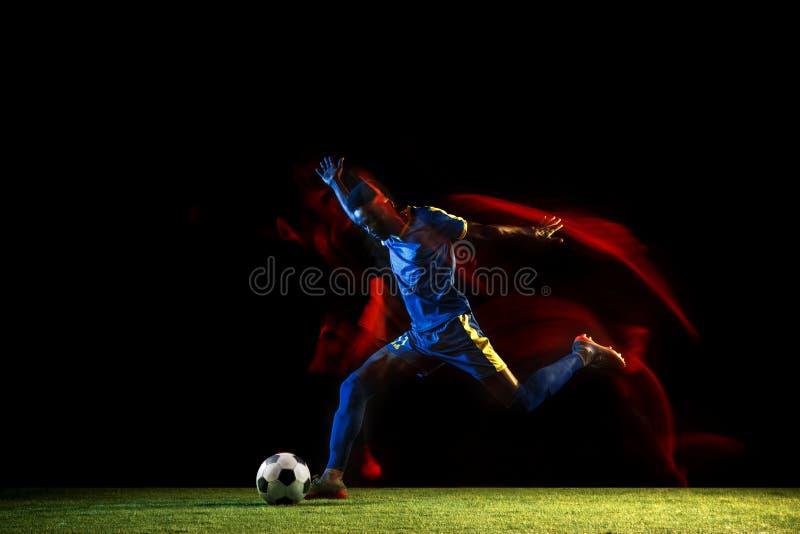 Jugador de fútbol de sexo masculino que golpea la bola con el pie en fondo oscuro en luz mezclada fotos de archivo libres de regalías