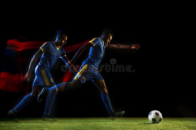 Jugador de fútbol de sexo masculino que golpea la bola con el pie en fondo oscuro en luz mezclada foto de archivo