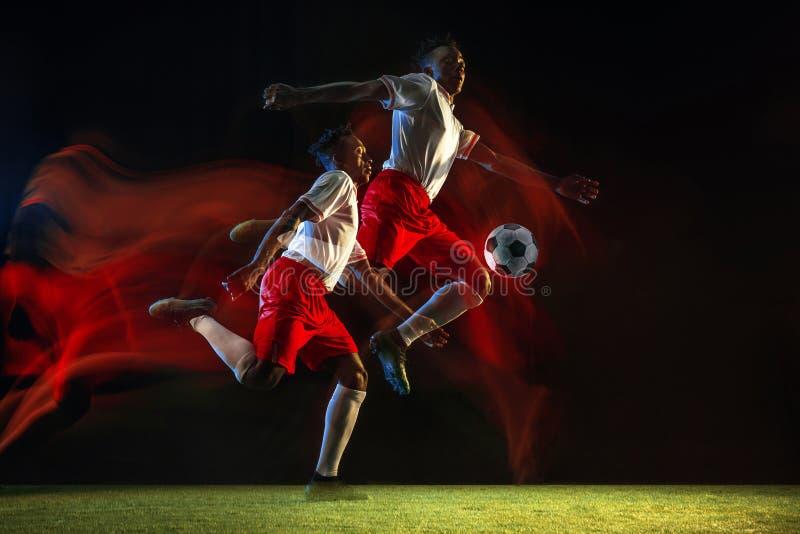 Jugador de fútbol de sexo masculino que golpea la bola con el pie en fondo oscuro en luz mezclada imágenes de archivo libres de regalías