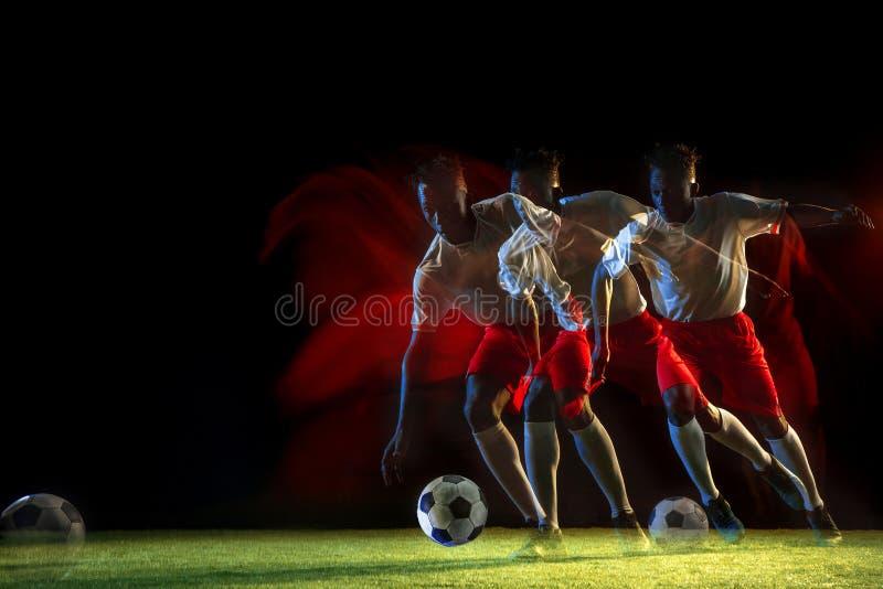 Jugador de fútbol de sexo masculino que golpea la bola con el pie en fondo oscuro en luz mezclada imagenes de archivo