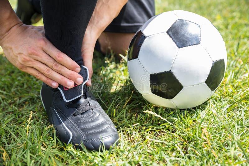 Jugador de fútbol de sexo masculino que sufre de herida en el tobillo imágenes de archivo libres de regalías
