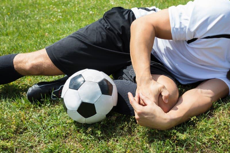 Jugador de fútbol de sexo masculino que sufre de lesión de rodilla imagen de archivo libre de regalías
