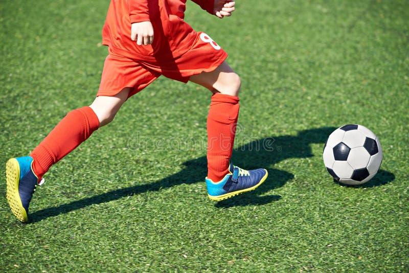 Jugador de fútbol y bola del niño en campo de fútbol foto de archivo
