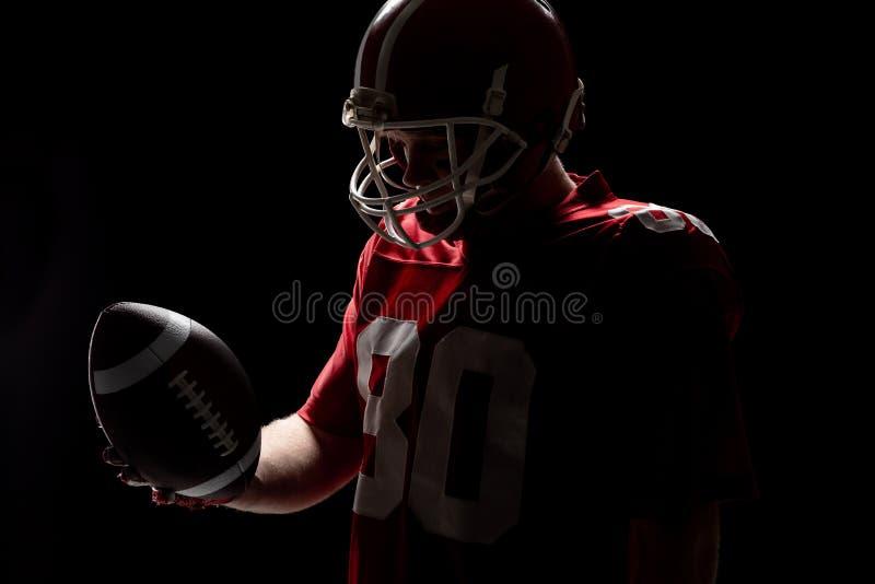 Jugador de f?tbol americano con el helmat que mira la bola de rugbi imágenes de archivo libres de regalías