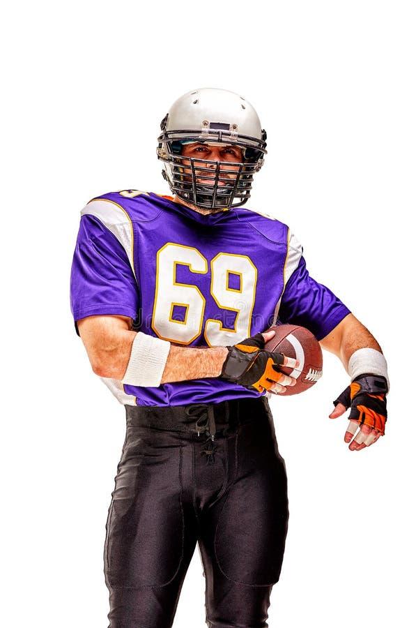 Jugador de f?tbol americano que presenta con la bola en fondo negro Formato cuadrado Fútbol americano del concepto, retrato imagen de archivo libre de regalías