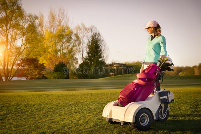 Jugador de golf femenino con la bolsa de golf fotografía de archivo