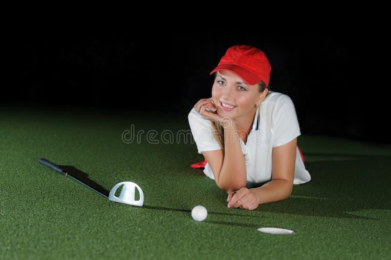 Jugador de golf femenino joven en campo artificial en el mini club de golf imagenes de archivo