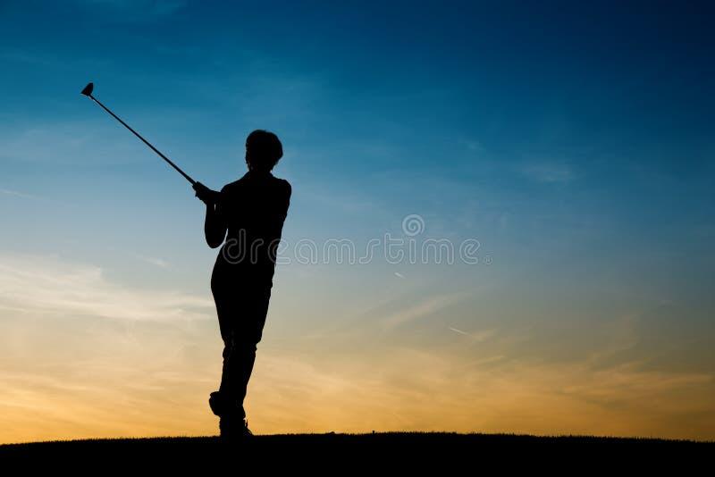 Jugador de golf femenino mayor en la puesta del sol imagenes de archivo