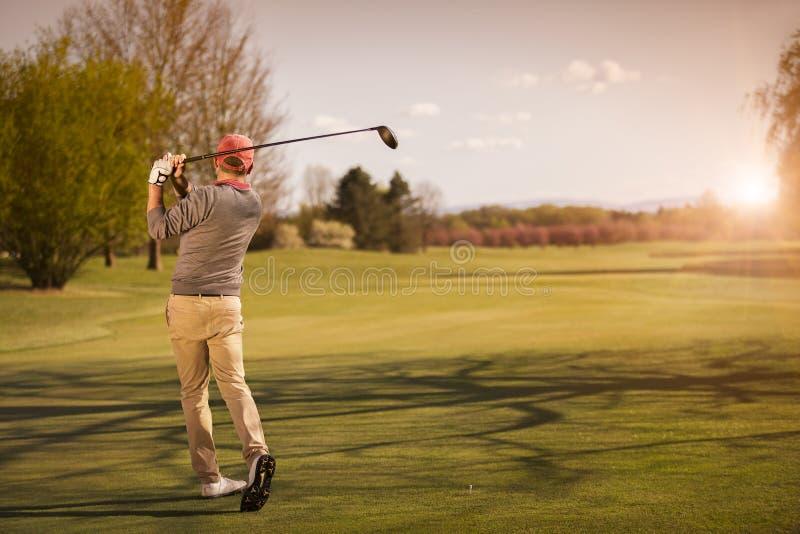 Jugador de golf masculino en la puesta del sol imágenes de archivo libres de regalías