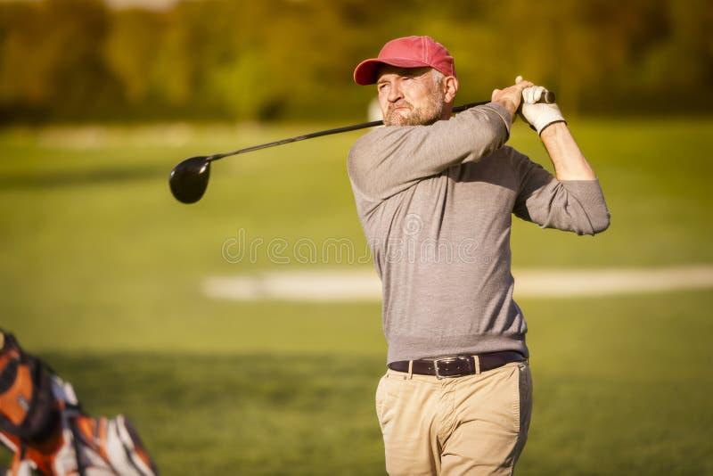 Jugador de golf masculino que junta con te apagado con el club foto de archivo libre de regalías