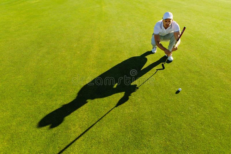 Jugador de golf que apunta el tiro con el club en curso foto de archivo