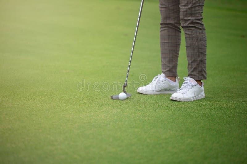 Jugador de golf que pone en verde y pelota de golf cerca del agujero fotos de archivo