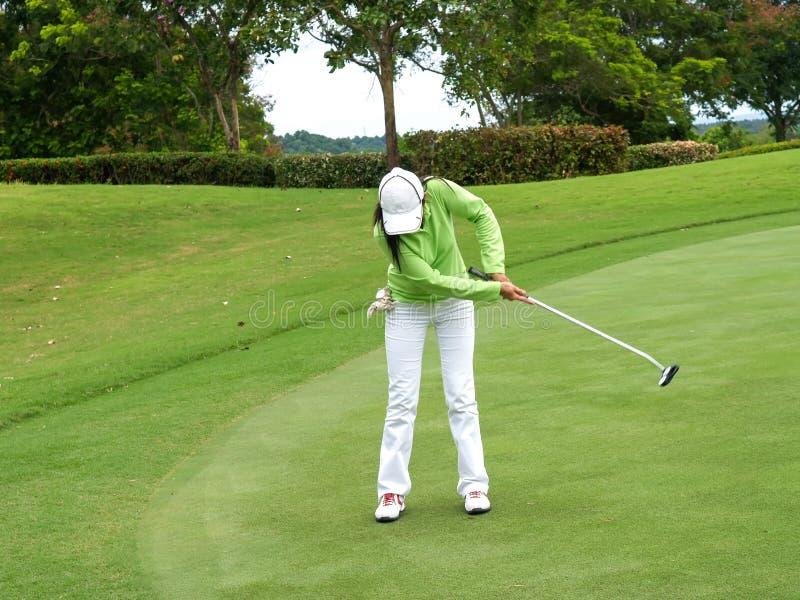 Jugador de golf sonriente de la mujer que pone con éxito la bola en verde foto de archivo