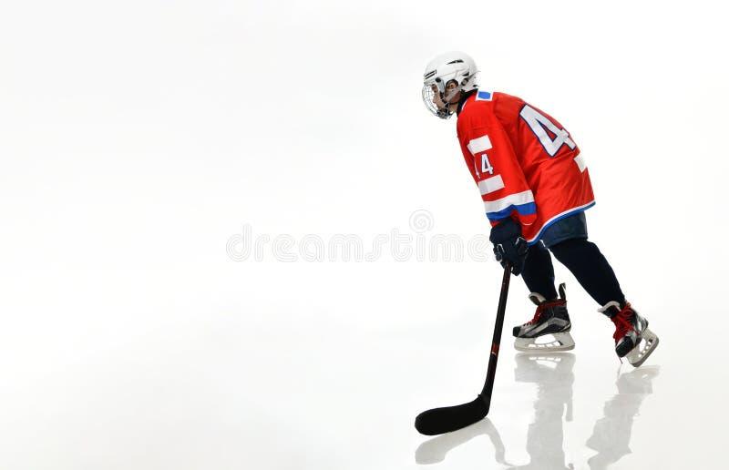 Jugador de hockey del muchacho en silueta del estudio en el fondo blanco foto de archivo
