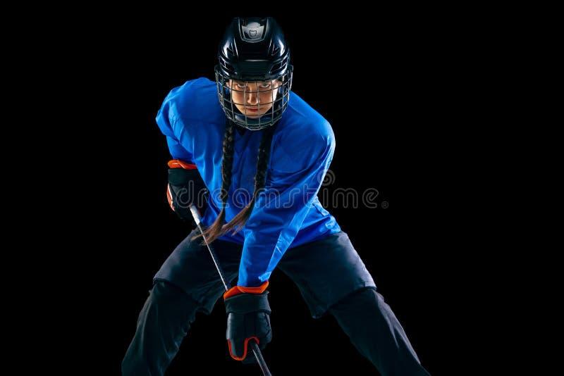 Jugador de hockey femenino joven con el palillo aislado en fondo negro imagenes de archivo