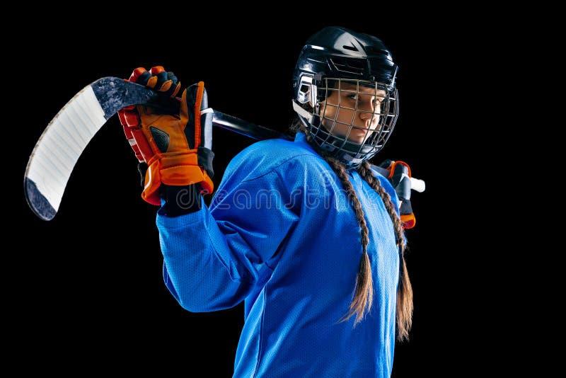 Jugador de hockey femenino joven con el palillo aislado en fondo negro foto de archivo libre de regalías
