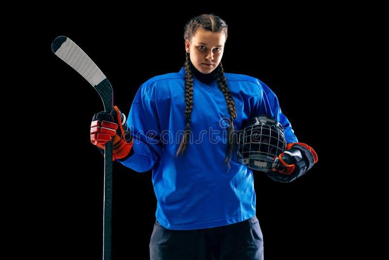 Jugador de hockey femenino joven con el palillo aislado en fondo negro foto de archivo