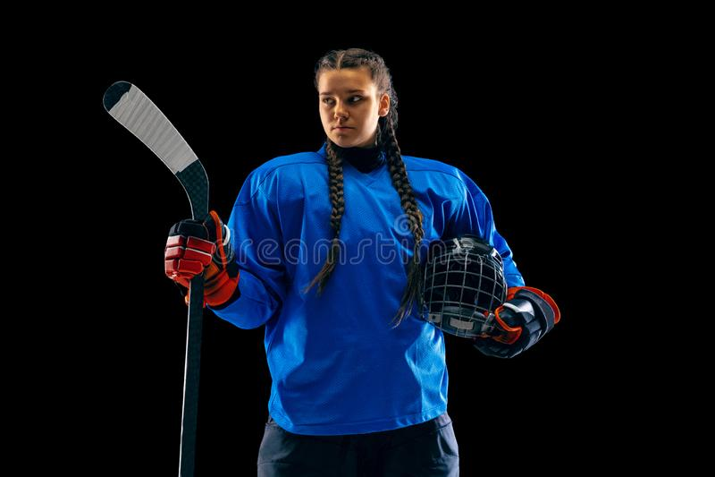 Jugador de hockey femenino joven con el palillo aislado en fondo negro fotos de archivo libres de regalías
