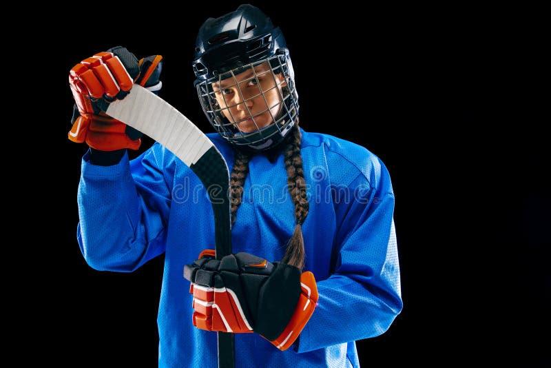 Jugador de hockey femenino joven con el palillo aislado en fondo negro imagen de archivo libre de regalías