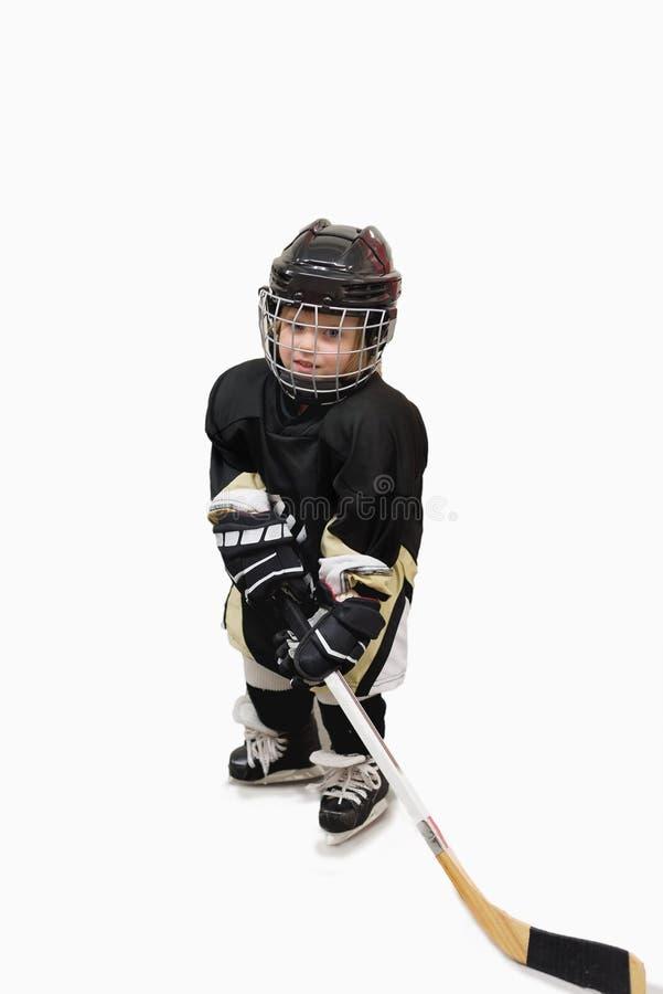 Jugador de hockey lindo aislado del niño en el equipo lleno del hockey Casco, guantes, palillo fotografía de archivo