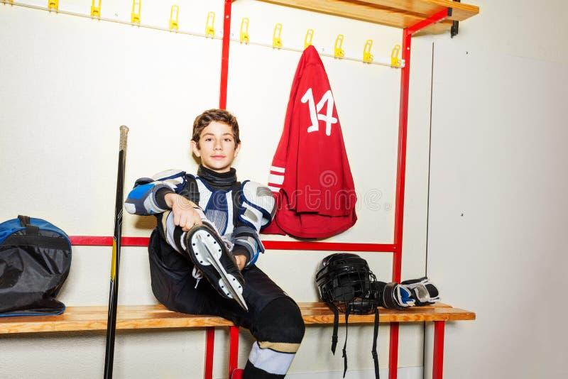Jugador de hockey que pone en patines de hielo en vestuario foto de archivo libre de regalías