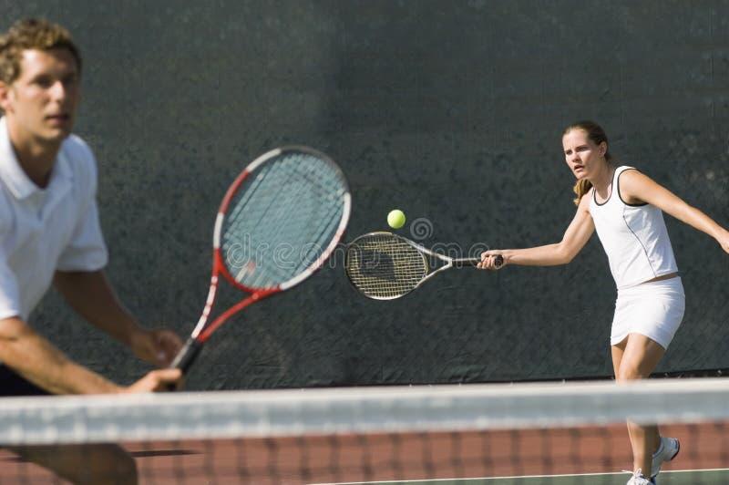 Jugador de los dobles mezclados que golpea la pelota de tenis fotos de archivo