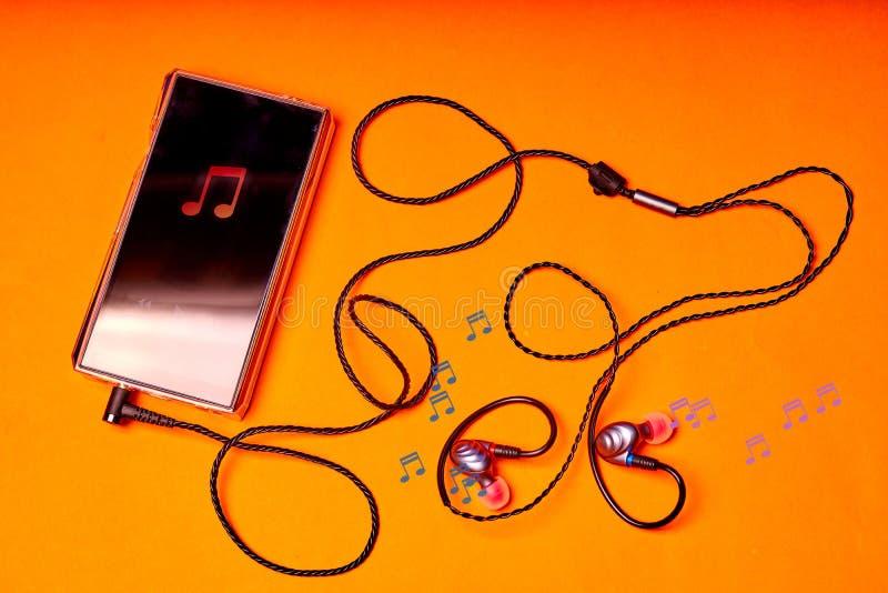 Jugador de música portátil en fondo anaranjado con los auriculares y el alambre imagenes de archivo