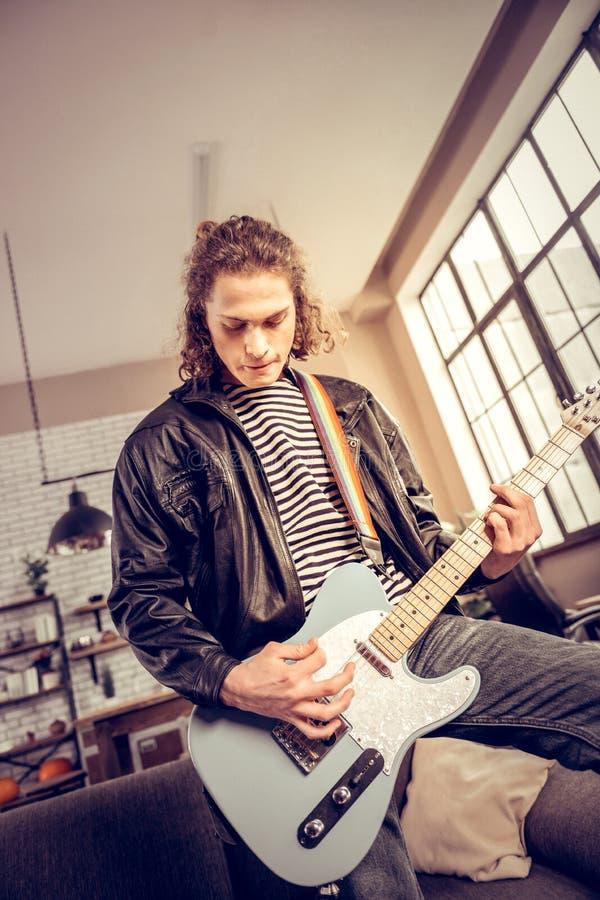Jugador de música rock oscuro-cabelludo rizado que compone la nueva canción fotos de archivo libres de regalías