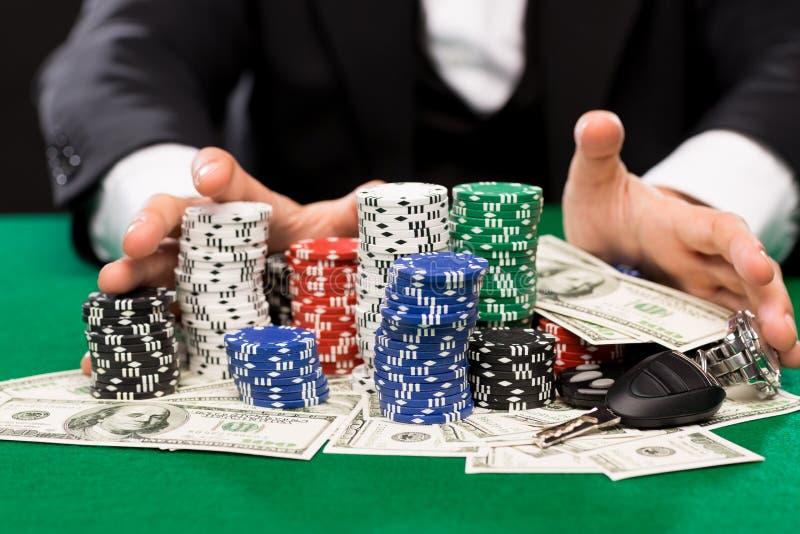 Jugador de póker con los microprocesadores y dinero en la tabla del casino fotografía de archivo