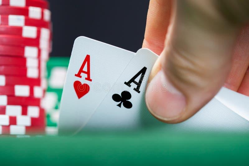 Jugador de póker que levanta las esquinas de dos tarjetas fotos de archivo libres de regalías