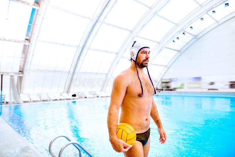 Jugador de polo del agua en una piscina foto de archivo