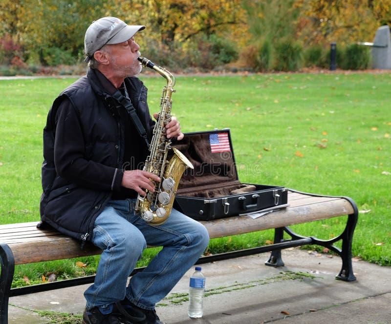 Jugador de saxofón en el parque del otoño, Oregon imagen de archivo