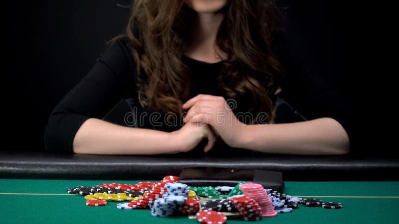 Jugador de sexo femenino hermoso que apuesta todos los microprocesadores y dinero del casino en juego de póker aventurado foto de archivo libre de regalías