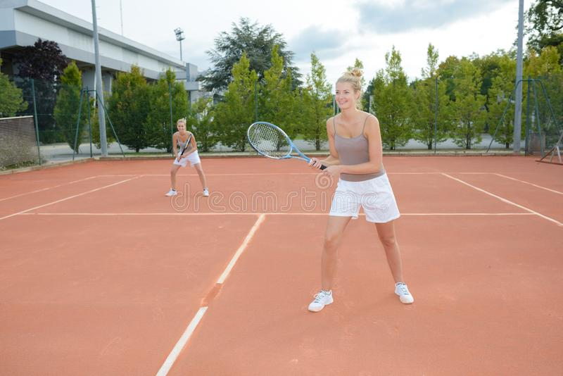 Jugador de tenis dos que juega dobles en la pista de tenis imagenes de archivo