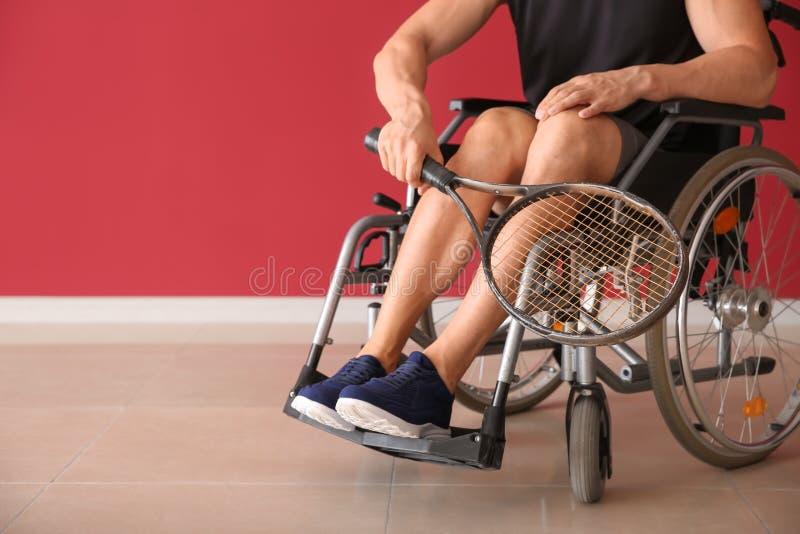 Jugador de tenis joven que se sienta en silla de ruedas contra la pared del color imagen de archivo
