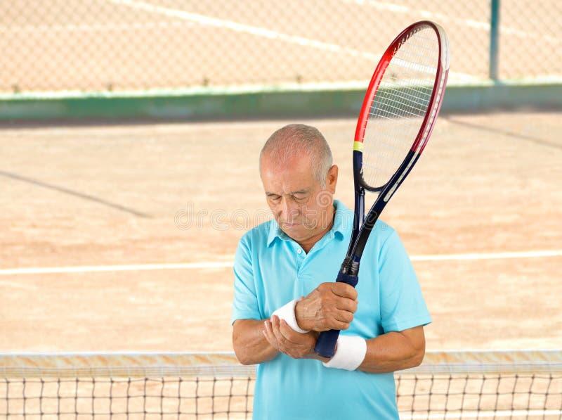Jugador de tenis mayor con dolor de la muñeca imagenes de archivo