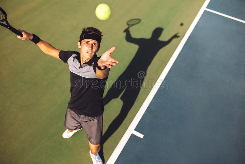 Jugador de tenis que sirve la bola en un partido imagen de archivo