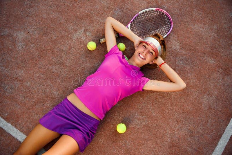 Jugador de tenis de sexo femenino joven cansado pero sonriente en mentiras uniformes rosadas en la pista de tenis al aire libre c fotografía de archivo