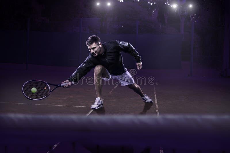 Jugador de tenis sobre hierba en la acción imagenes de archivo