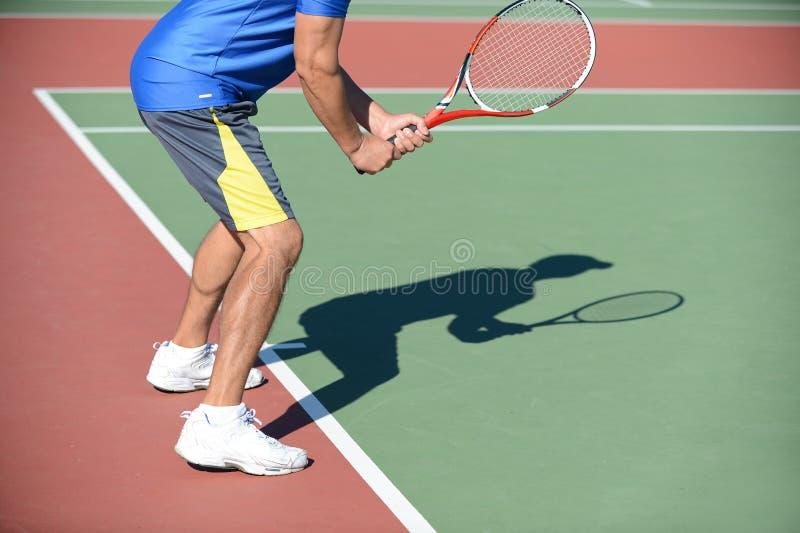 Jugador de tenis y sombra en corte fotografía de archivo libre de regalías