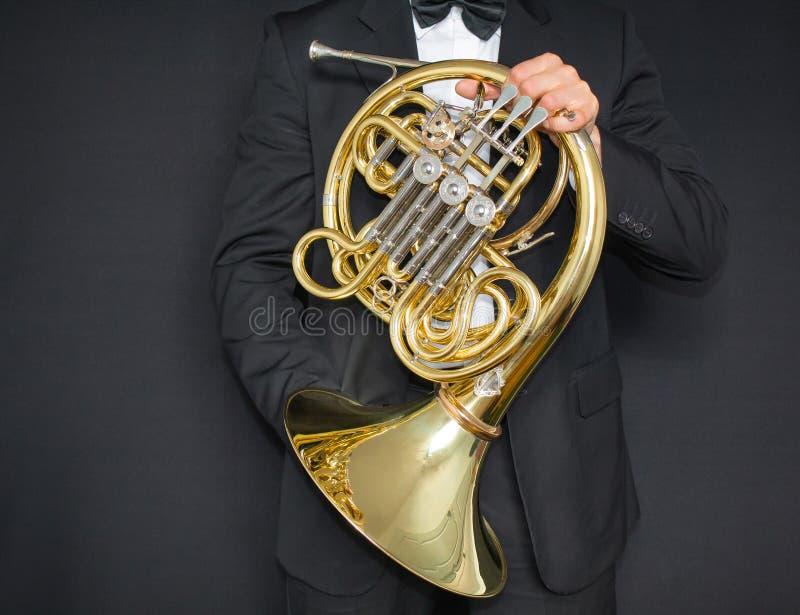 Jugador de trompa Cuerno del instrumento de música en las manos del hombre del hornist A en un traje con un instrumento musical imagen de archivo