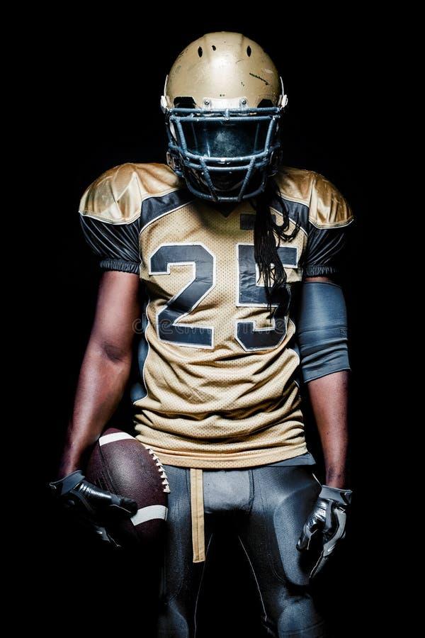 Jugador del deportista del fútbol americano aislado en fondo negro fotos de archivo