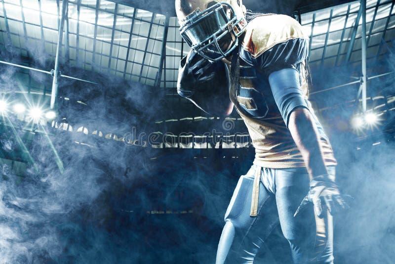 Jugador del deportista del fútbol americano en el estadio que corre en la acción imagenes de archivo
