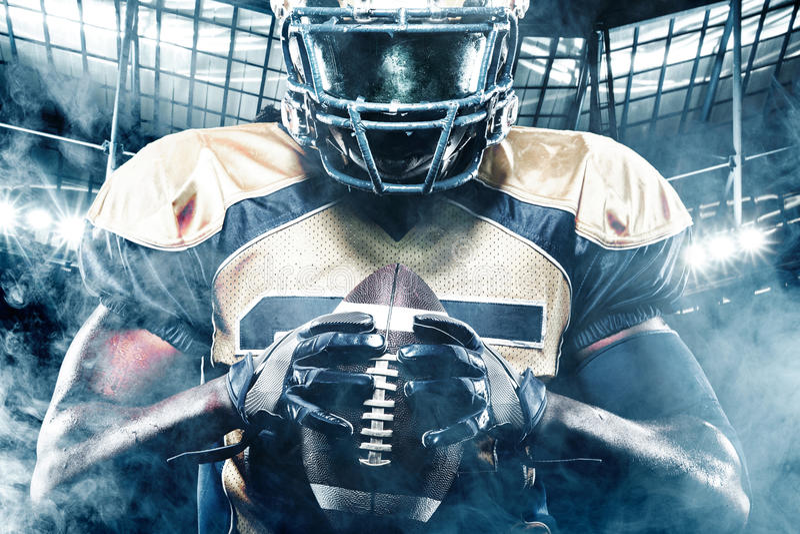 Jugador del deportista del fútbol americano en estadio con las luces en fondo foto de archivo libre de regalías