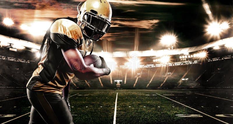 Jugador del deportista del fútbol americano en el estadio que corre en la acción Papel pintado del deporte con el copyspace foto de archivo