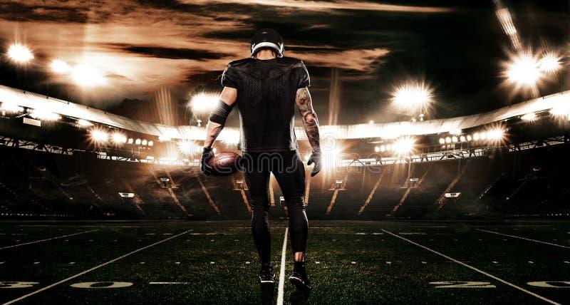 Jugador del deportista del fútbol americano en estadio Bandera y papel pintado de los deportes con el copyspace imagen de archivo libre de regalías