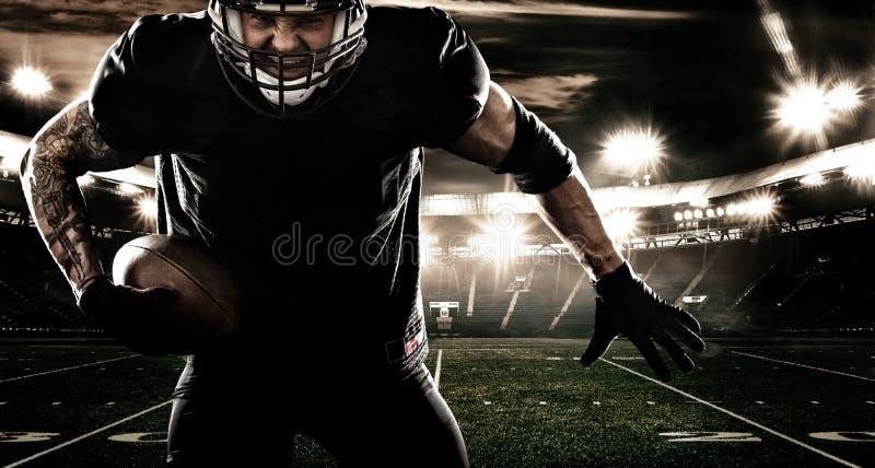 Jugador del deportista del fútbol americano en estadio Bandera y papel pintado de los deportes con el copyspace imagen de archivo