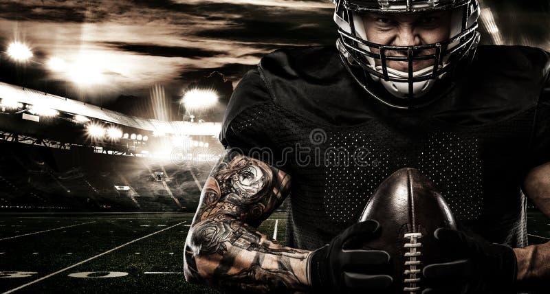 Jugador del deportista del fútbol americano en estadio Bandera y papel pintado de los deportes con el copyspace fotos de archivo