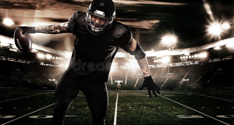 Jugador del deportista del fútbol americano en estadio Bandera y papel pintado de los deportes con el copyspace imágenes de archivo libres de regalías