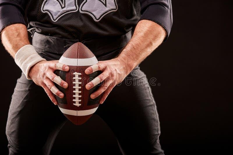 Jugador del deportista del fútbol americano en estadio con las luces en fondo negro fotografía de archivo libre de regalías